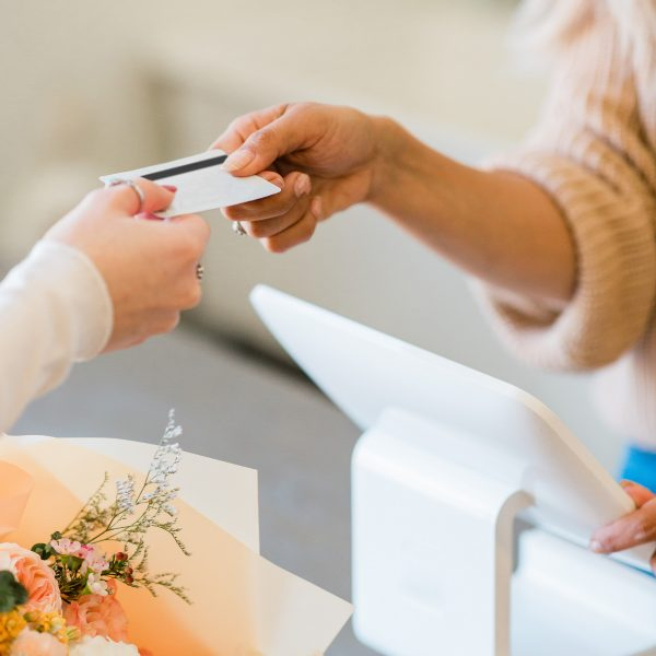 woman handing credit card to another woman
