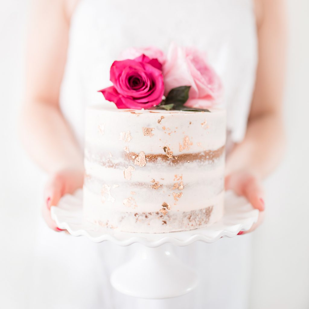 Woman holding wedding cake with pink flower